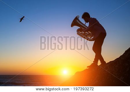 Silhouette of a young musician playing the Tuba on rocky sea coast during sunset.