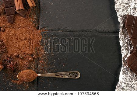 Cocoa and coffee beans vintage spoon with cocoa powder cinnamon sticks and broken chocolate slices on a dark slate background with copy space. Top view