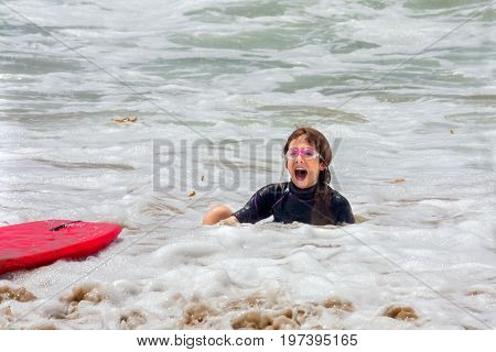 A young girl sits with an open mouth surprised look in shallow foamy ocean water after she fell off her boogie board.