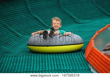 Smiling boy slides down in inflatable ring