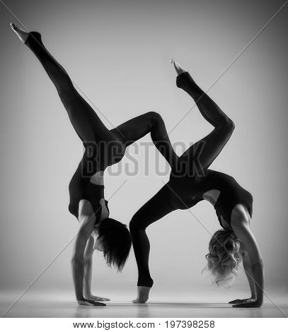 Portrait of two fit acrobatic women posing on light gray background in black white