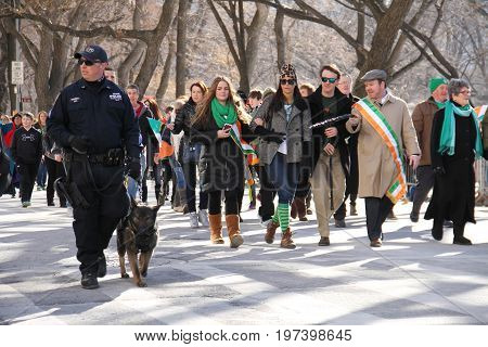 Manhattan, New York March 17, 2017: A part of parade and k-9 dog on st patrick's day and trees at Central Park