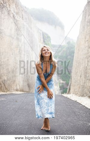 Vertical portrait of an attractive smiling girl in light-blue dress is standing cross-handed on the road between mountains and looking in the camera
