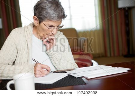 Senior Woman Paying Bills At Home In Her Office