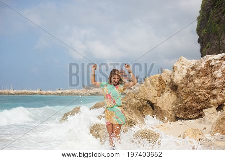 Horizontal portrait of beautiful excited blonde girl in colorful dress is standing on the beach in front of stones and looking down with hands in the air
