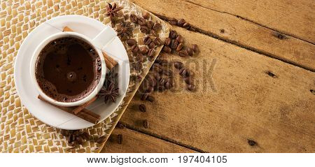 Cup of coffee with cinnamon sticks anise and arabica coffee beans on old wooden rustic background with copy space.