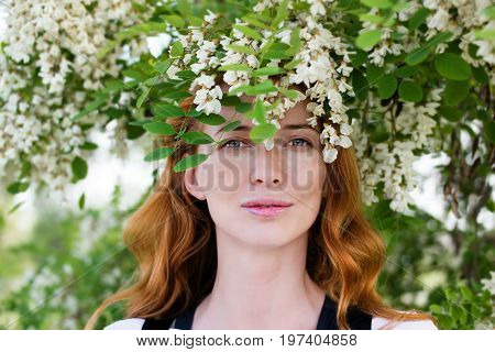 Portrait of a beautiful young red-haired woman among the flowering branches of a acacia in the spring garden