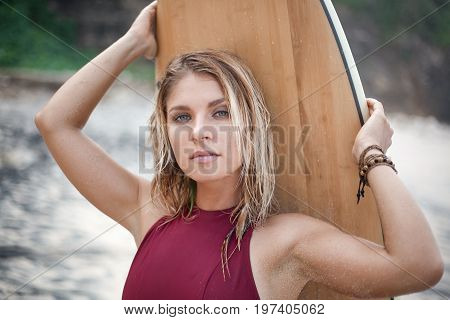 Horizontal close-up portrait of an attractive surf girl in dark-red swimming suit holding a surfboard on the beach and looking in the camera