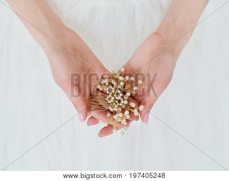 Hairpins in the hair. Wedding. The bride is holding a wedding pendant in her hands