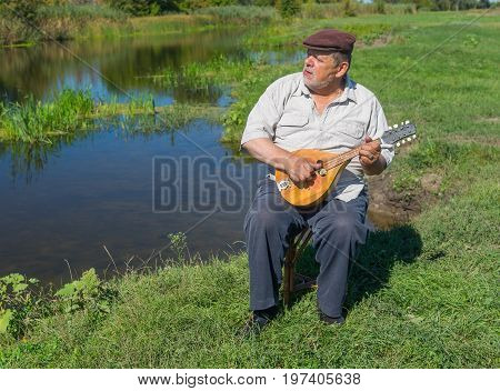 Senior man having rest on a riverside sitting on a wicker stool singing and playing mandolin