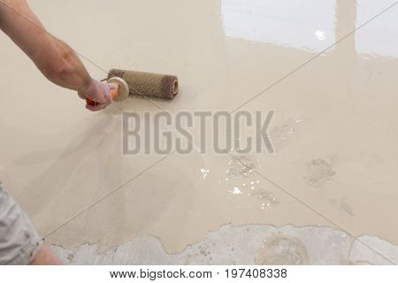Repair work. Pouring floors in the room. Fill screed floor repair and furnish. Worker align cement with roller.
