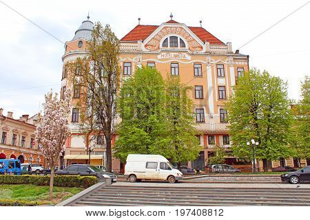 CHERNIVTSI, UKRAINE - APRIL 22, 2017: Former Hotel Bristol from the Philharmonic square where tourists and locals like to feed the pigeons
