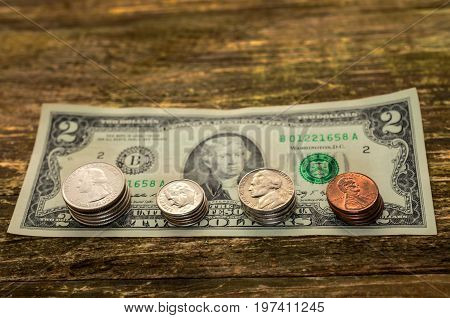 Concept of saving money in a crisis and home finances. Finance and savings. Banknote is two American dollars and coins of different denominations in the amount of two dollars lying on top. On a wooden table. With a focus in the foreground.