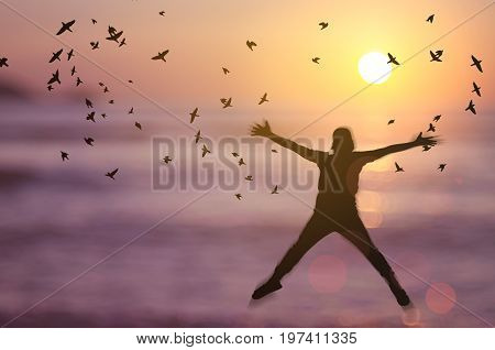Freedom And Feel Good Concept. Copy Space Of Silhouette Happy Man Jumping On Blur Tropical Sunset Be