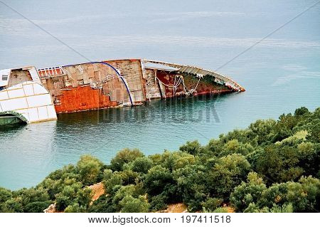 Abandoned and rusty shipwreck near coastline. Greece