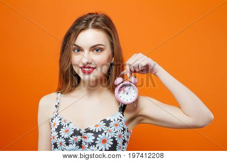Attractive Brunette With Pink Clock In Hand Posing On Orange Background In Studio. Time Concept.