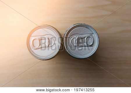 Top view of aluminum cans in droplets of water on wood .