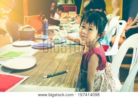 Child looking at camera and prepare paint her palm on art class. Education and learning concept. Strengthen the imagination of child for learning and education concepts. Vintage tone. Selective focus.