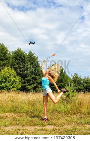 The Blonde Girl With A Fly Swatter Drives Away Drone, Against Blue Sky With White Clouds