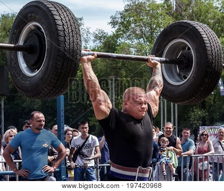 Almaty , Kazakhstan - May 28, 2017. strong man raises a heavy barbell. City fesitwal sport on the street for a healthy lifestyle. Sports contests for arm-wrestling, heavy lifting, tug-of-war