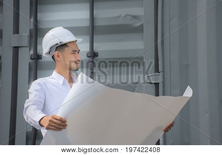 Engineers, architects looking at the planner are happy with the job/Architect design/Young Asia man engineer wearing safety white helmet checking construction site building,Construction concept.