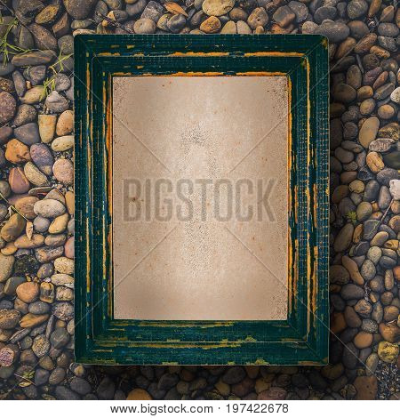 Top view of old picture frame with paper blank space on beach stones.