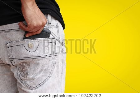 Male hand putting wallet in back pocket of jeans on yellow background with copy space.