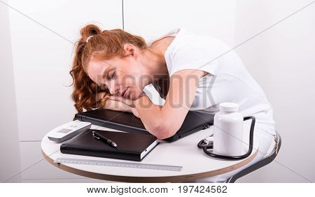 Young red-haired doctor has fallen asleep because of overworked