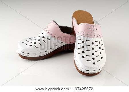 Beautiful modern pair of clogs isolated on grey background
