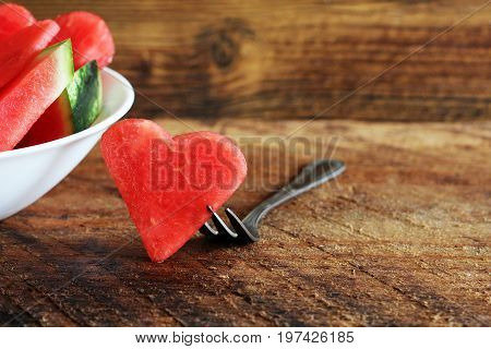 Fresh sliced watermelon on wooden background. Slices form of heart. One slice on fork .