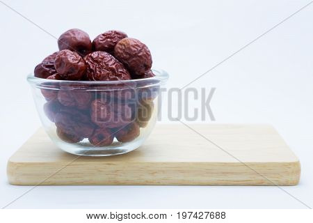 Chinese dried red jujube on wooden board on white background