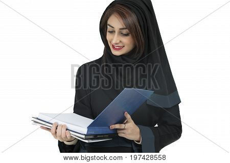 Arabic student wearing abaya holding blue book