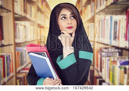 Arabic student wearing hijab holding a book in a library