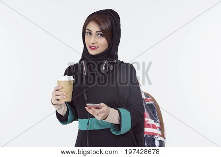 arab student wearing hijab holding mobile and coffee cup