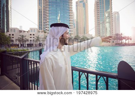 Arab young man Showing Dubai skyline with hand