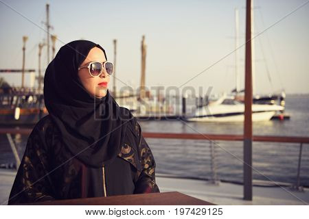 Arab woman wearing sunglasses enjoying her evening in Dubai.