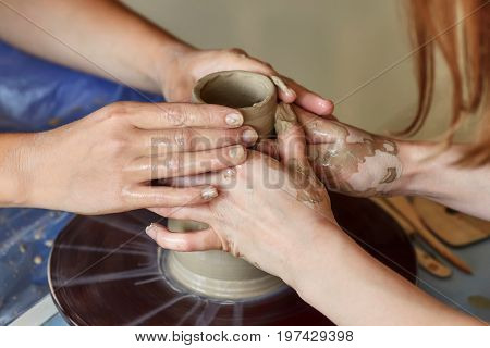 Hands of two people create pot on potter's wheel. Teaching pottery carftman's hands guiding