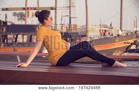 Pregnant woman posing in yellow t-shirt. young happy pregnant woman relaxing and enjoying life in Dubai