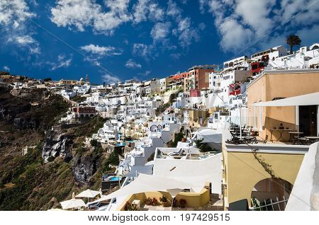 Fira, Thira town, Santorini Cyclade islands, Greece. Beautiful view of the town with white buildings, blue church\'s roofs and many coloured flowers.