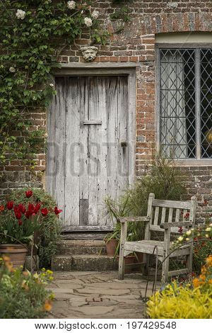 Quintessential Old English Country Garden Image Of Wooden Chair Next To Vintage Back Door