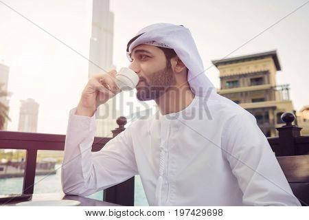 Arab man drink coffee in coffee shop in Dubai