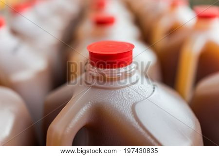 Rows Of Plastic Gallon Jars On Display Filled With Apple Cider
