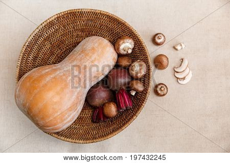 Purple Beets,Orange Pumpkin,Fresh Mushrooms in the Rattan Braided Big Plate on the Linen Tablecloth.Autumn Garden's Vegetable Background.Top View