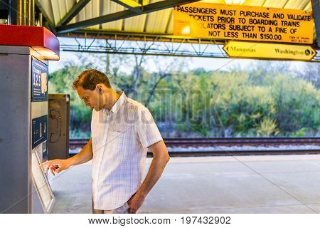 Burke, Usa - April 16, 2017: Young Man Buying Tickets In Machine At Burke Centre Train Station Platf