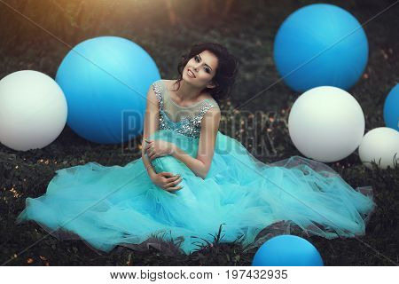 Beautiful girl graduate in a blue dress is sitting on the grass near a large blue and white balloons. Cheerful elegant young woman in a beautiful dress in the park. Lovely girl with a beautiful smile.