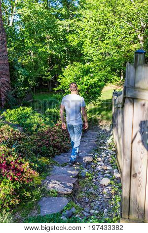 Back of young man walking on garden path outside on rocks in sunny summer