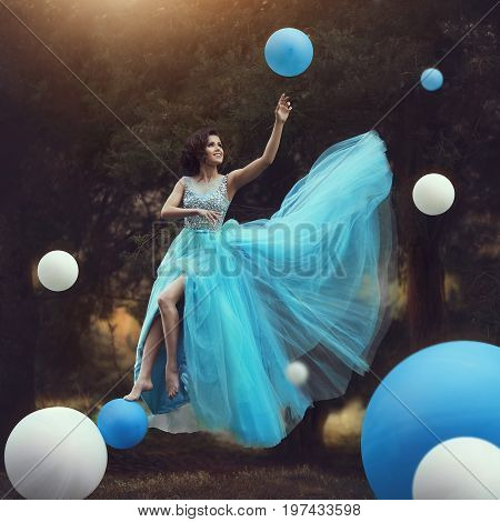 The Woman levitates. A beautiful girl in a blue fluffy gown Leets along with balloons. Dynamic art photography. Fantasy and Surrealism. The girl flies like in a fairy tale.