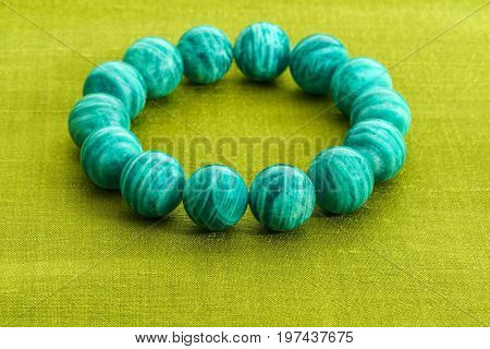 Beautiful Amazonite or Amazon stone beads in bracelet on green Thai silk background