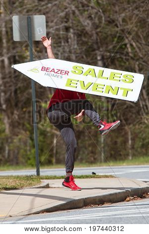ATLANTA, GA - MARCH 2017: A young man skillfully tosses a sign in the air as he promotes a home selling event with a sign on a street corner in Atlanta GA on March 25 2017.