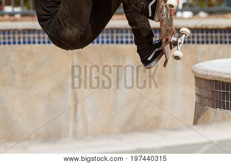 ATLANTA, GA - MARCH 2017:  A teenager's lower body is seen as he makes a jump in a skateboard park bowl at Brook Run Park in Atlanta GA on March 25 2017.